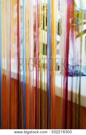 Multicolor String Curtain ( Filament Curtain ) On Window. Home Plants In The Background. Selective F