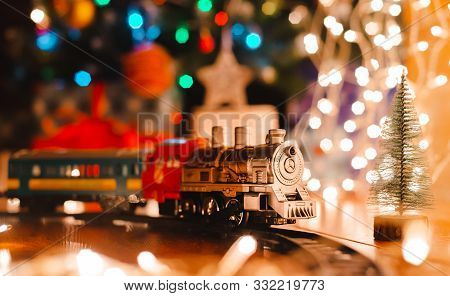Toy Vintage Steam Locomotive On The Floor Under A Decorated Christmas Tree On A Background Of Bokeh