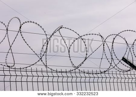 Barbed Wire Against The Cloudy Sky. Barbed Wire Fencing From The Prison Fence. The Concept Of Captiv