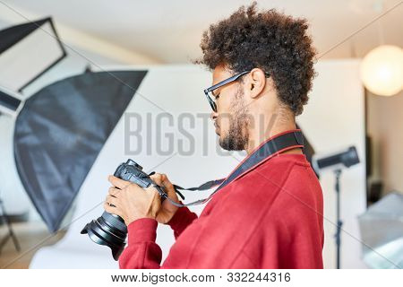 Young photographer or photo student is examining settings on his camera