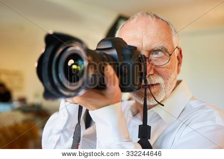Senior as a professional photographer with camera during the photo shoot