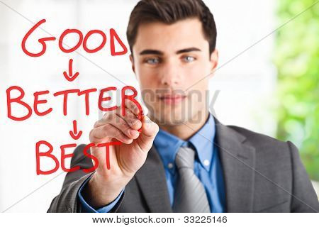 Handsome businessman writing a motivational concept on the screen