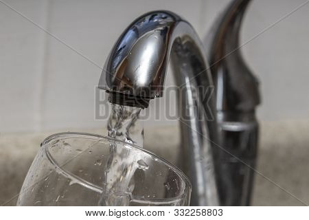 Glass At Water Tap And Filling Water With Lead Contamination