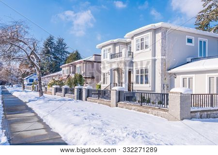 A perfect neighbourhood. Houses in suburb at Winter in the north America. Luxury houses covered nice snow. Aerial drone view. 4K.