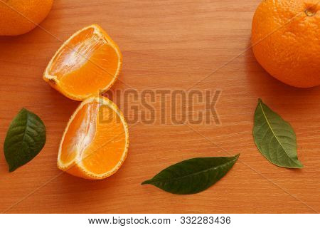 Orange Ripe Chinese Tangerines Slices  Tangerines With Green Leaves Wooden Table Background Close-up