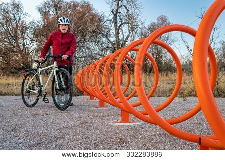 Senior male cyclist with a touring bike is approaching colorful helix bike rack along a trail in Fort Collins, Colorado - outdoor activity and bike commuting concept