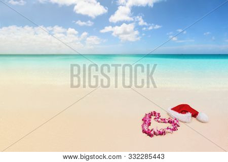 Christmas winter holidays paradise beach travel destination for honeymoon vacation background. Landscape with idyllic pristine blue ocean water and white sand. Lei flower necklace.