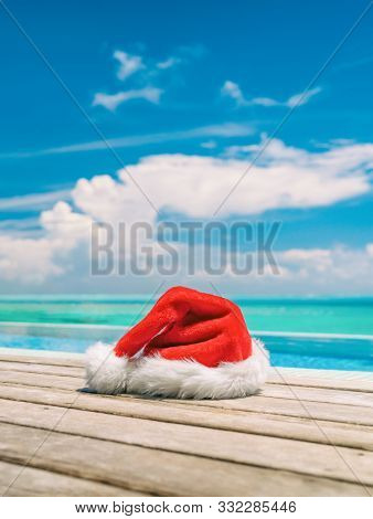 Christmas winter holidays santa hat near swimming pool of Caribbean resort travel vacation destination. Vertical backdrop of paradise vacations.