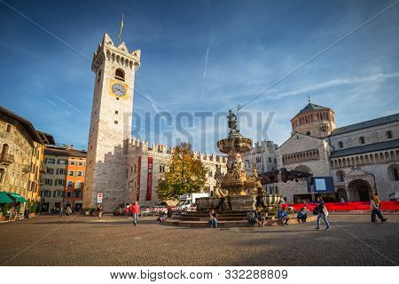 Trento, Italy - October 25, 2019: People walking at the fountain of Neptune on Piazza Duomo in Trento, South Tyrol. Italy