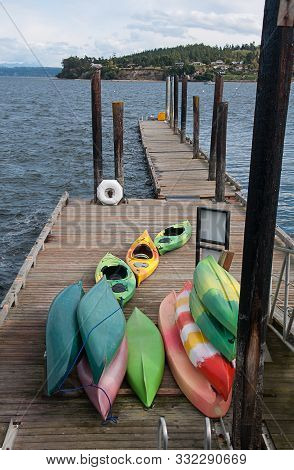 Colorful kayaks on dock taken in Coupeville Washington in the Pacific Northwest landscape.  Puget Sound ocean water with a point of land in the distance. poster