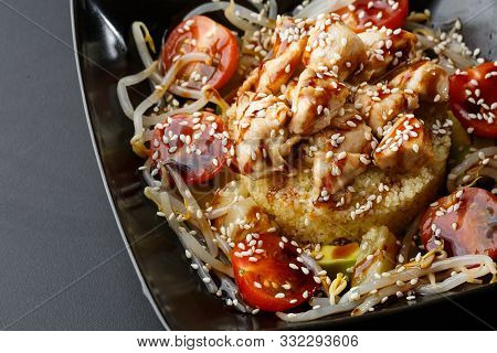 Couscous Dish With Chicken, Turkey , Tomatoes, Wheat Sprouts And Unagi Sauce On Plate On Black Backg