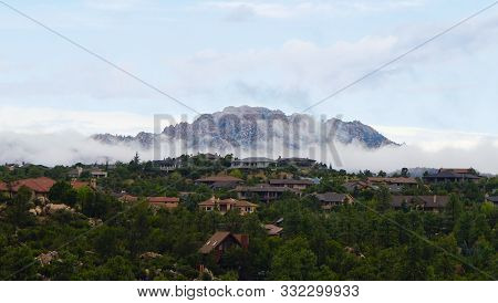 Granite Mountain Clothed In Low Misty Clouds As Morning Comes To Northern Arizona.