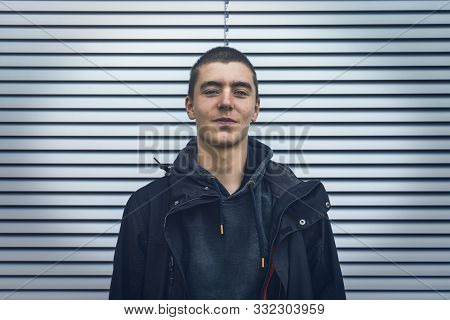 Portrait Of A Smiling Young Man In Front Of A Silver Roller Shutter