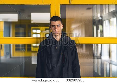 Portrait Of A Smiling Young Man In Front Of Yellow Windows
