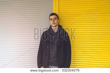Portrait Of A Young Man In Front Of A Yellow And Gray Roller Shutter