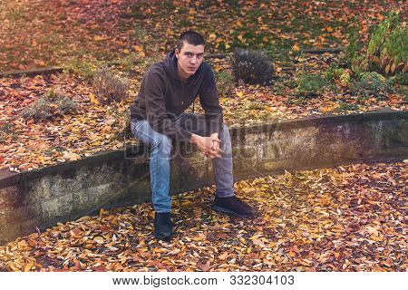 Portrait Of A Casual Young Man Sitting On A Wall With Autumn Leaves