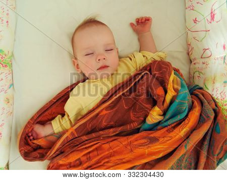The Little Baby Sleeps Sweetly In His Crib In A Plaid, In A Sling, In A Blanket. The Baby Girl Sleep