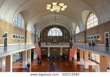 ELLIS ISLAND, NY - 04 NOV 2019: Tourists at the Great Hall inside the Ellis Island National Museum of Immigration.