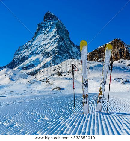 Ski in winter season, mountains and ski equipments on the freshly groomed slope of snowy mountains in sunny day, Zermatt, Switzerland.