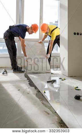 Workers Are Installing A Large Ceramic Tile On The Floor.