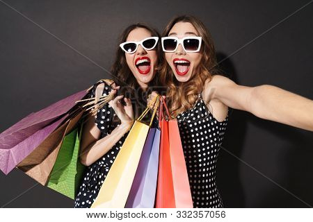 Image of two posh young girls in sunglasses taking selfie on cellphones and holding shopping bags isolated over black background