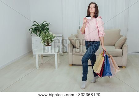Young Caucasian Girl Is Standing With A Lot Of Bags From Shop And Credit Card In Her Hands, Looking