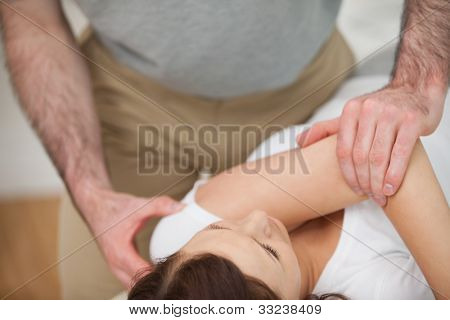 Osteopath making a joint mobilization in his medical office poster