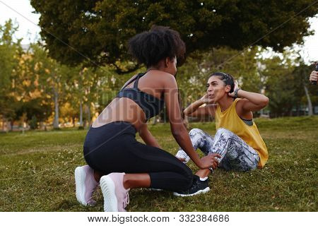 Fit Young Woman Doing Crunches Exercise With Her Female Friends During Athlete Workout In The Park -