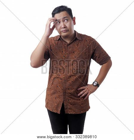 Portrait Of Young Confused Asian Man Wearing Batik Shirt Shows Thinking Expression, Looking Up Conte