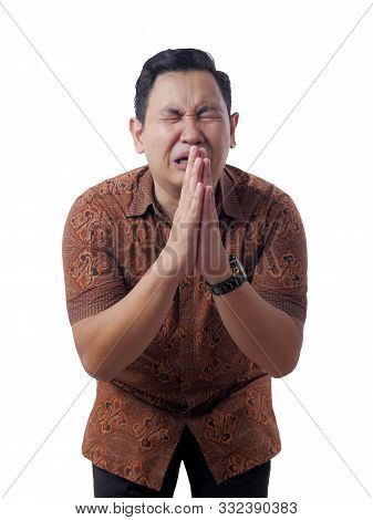 Young Asian Man Wearing Casual Batik Shirt Regret, Apologize Gesture. Close Up Body Portrait