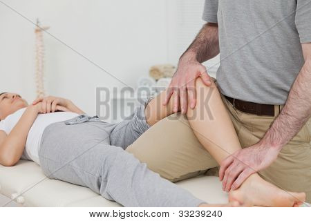 Woman lying on her back while a physiotherapist manipulates her leg in a physio room