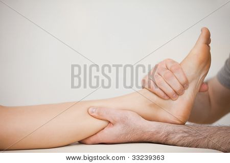 Muscle of a foot being massaged in a room poster