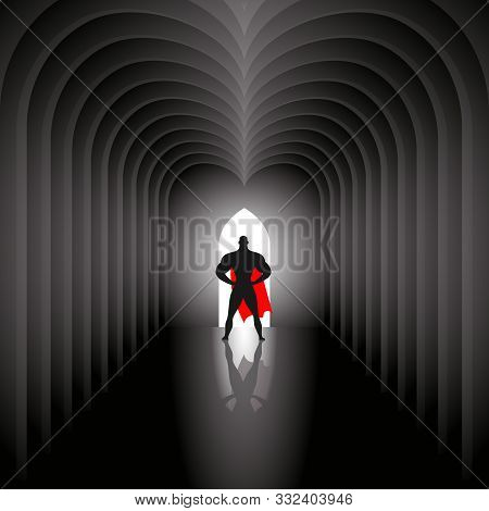 The Superhero In The Red Cloak Stands At The End Architectural Tunnel. The Light Comes From The Open