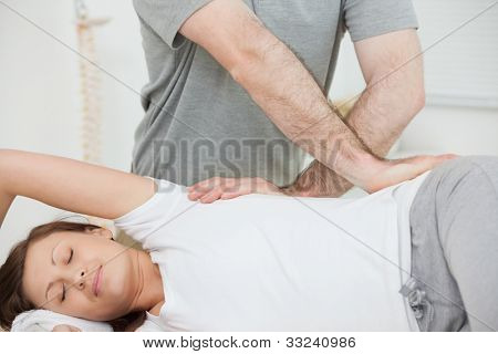 Smiling woman being massaged in a room