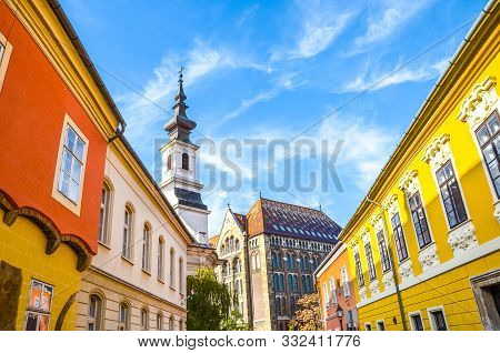 poster of Historical street and buildings with colorful facades in the historical center of Budapest, Hungary. Lutheran Church of Budavar in the background. Amazing old town of the Hungarian city. Tourist spot
