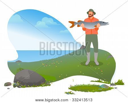 Bearded Fisherman Standing Near Lake And Poses With Caught Big Fish. Man With Green Wearing Hat And