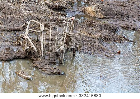 A metal shopping cart is tipped over in the mud at the edge of a river. The discarded basket is partly embedded in the dirt and water outside. poster