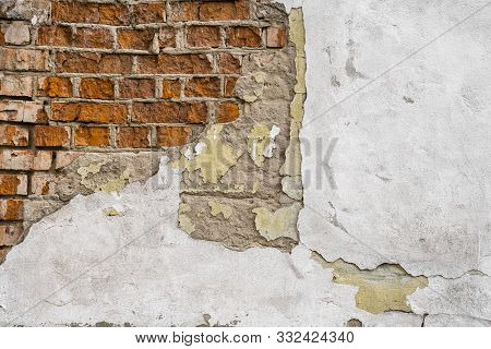 Cracked Concrete Vintage Brick Wall. Cracked Putty On The Wall And Brick That Looks Through The Crac