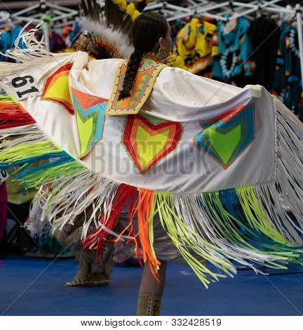 Native American Woman With Braided Hair Dancing At A Pow Wow With A White, Neon Orange And Yellow, R