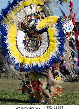 Close Up Of A Young Native American Man With A Headdress And Bustle With Yellow, White And Blue Feat