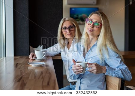 Eautiful Blonde With Glasses And Her Elderly Mother Are Sitting In A Cafe And Drinking Coffee. Mothe