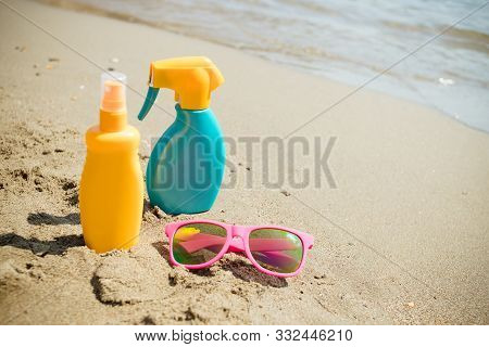 Sunscreen, Glasses On Sand Beach Background. Cosmetics For Safe Sunburn. Skin Care Concept. Healthy