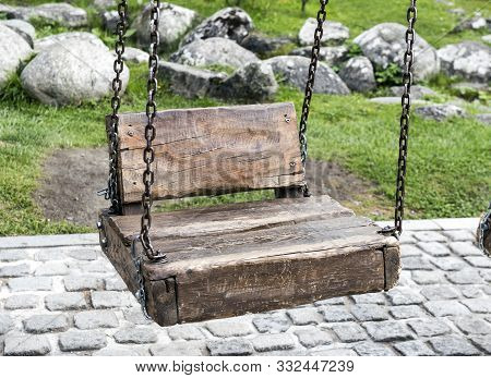 Swing On Chains. Swing On Chains With A Wooden Seat And A Wooden Back. In The Background Is Growing