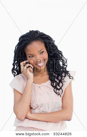 A young woman is smiling and talking on the mobile phone