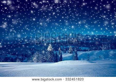 Beautiful Christmas Night With Snowfall. Christmas Holiday Landscape Of Mountains At Starry Night Wi