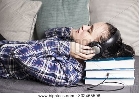Weird Strange, Relaxed Young Woman Laid Her Head On The Old Thick Books That She Kind Of Listens Thr