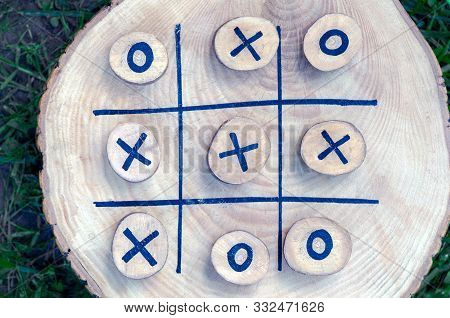 Tic Tac Toe Game On A Wooden Board With Wooden Tac Toe And Crosses. Winner Strategy, Winning Skill,