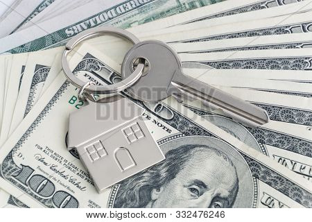 Home Keys And A Small House On Currencies Dollar Background. The Concept Of Renting Or Selling A Hou