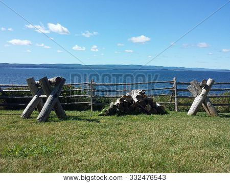 poster of Sawing logs on a wooden stand on a green lawn. Ocean view. Supports for cutting firewood and pile of wooden logs near wooden fence. Canada. Cut firewood Saws to saw.