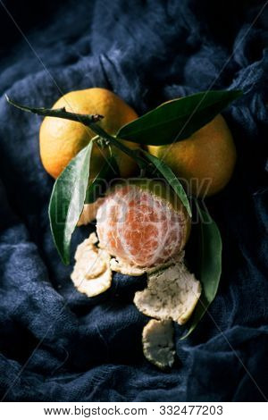 a bunch of mandarin oranges on a dark gray gauze fabric poster